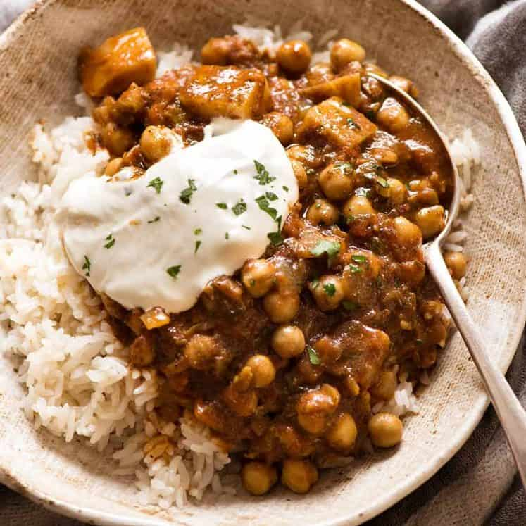 Photo of Chickpea Curry (Chana Aloo) in a bowl over coconut rice with a dollop of yogurt in a rustic bowl, ready to be eaten