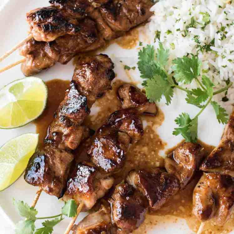 Honey Sriracha Chicken Skewers on a white plate with a side of coconut lime cilantro rice.