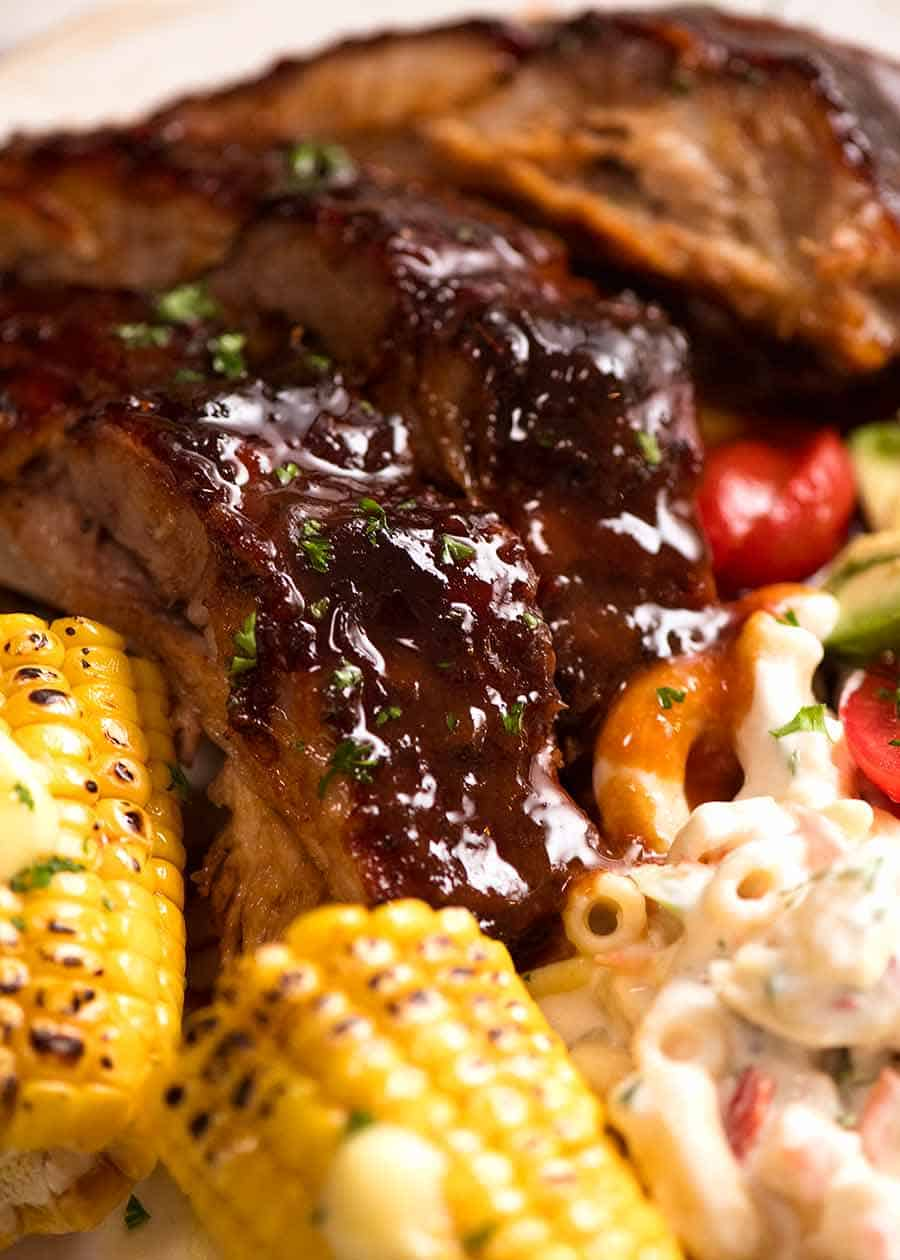 Close up of Oven Barbecue Pork Ribs dinner with a side of Macaroni Salad, corn and cucumber tomato salad