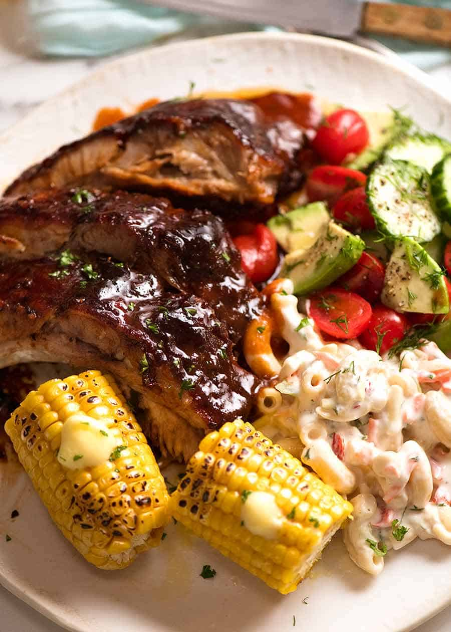 Oven Barbecue Pork Ribs dinner with a side of Macaroni Salad, corn and cucumber tomato salad