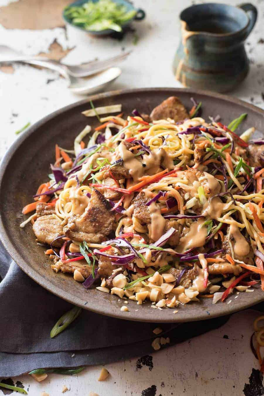 Satay Chicken Noodle Salad drizzled with peanut dressing in a rustic dark brown bowl.