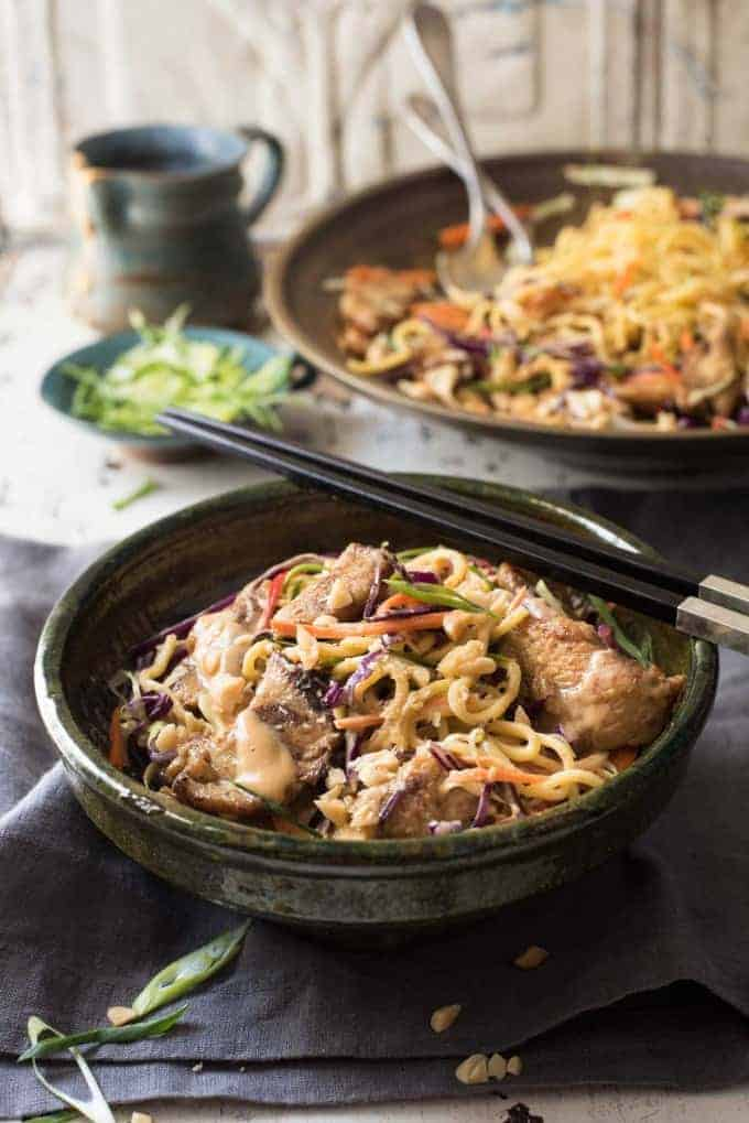 Satay Chicken Noodle Salad in a rustic ceramic green bowl with chopsticks resting on the edge, ready to be eaten.