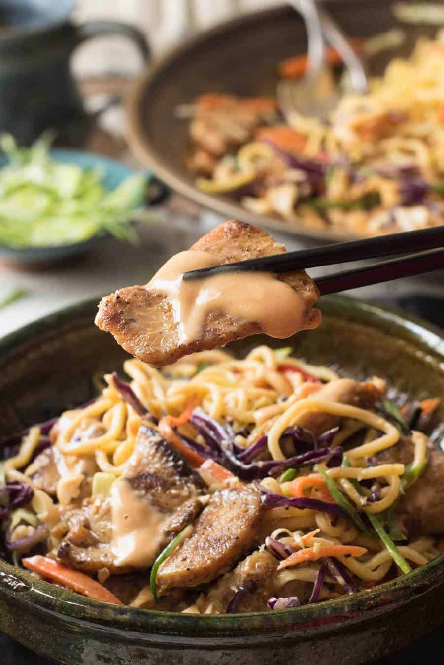 Close up of a piece of chicken drizzled with peanut dressing from a Satay Chicken Noodle Salad.
