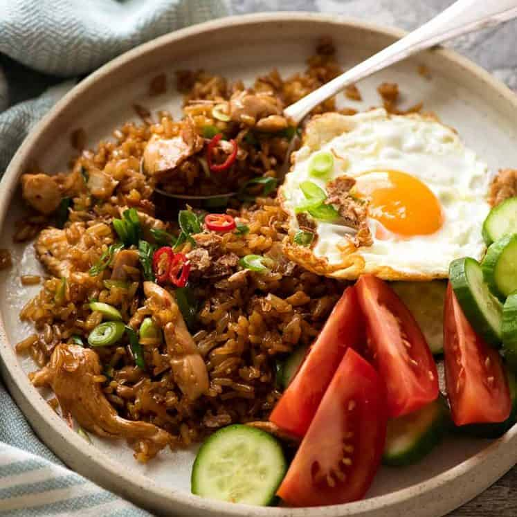 Nasi Goreng on a plate with a side of fried egg, tomato and cucumbers