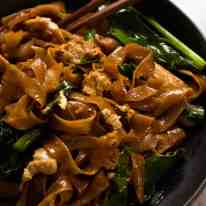 Close up of Pad See Ew noodles on a plate with chopsticks, ready to be eaten
