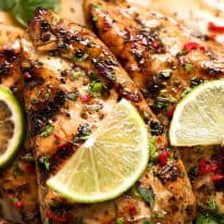 Close up of Lime Chicken on a plate, garnished with cilantro/coriander, chilli and fresh lime slices
