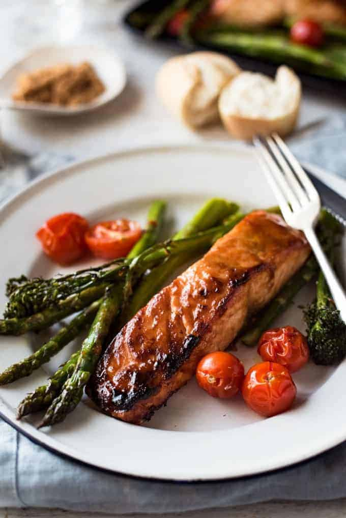 Spicy Brown Sugar Salmon on plate with asparagus and tomatoes