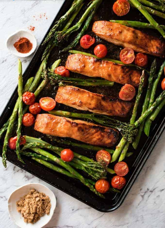 Spicy Brown Sugar Salmon on a tray with asparagus and tomatoes