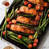 Spicy Brown Sugar Salmon on tray with asparagus and tomatoes