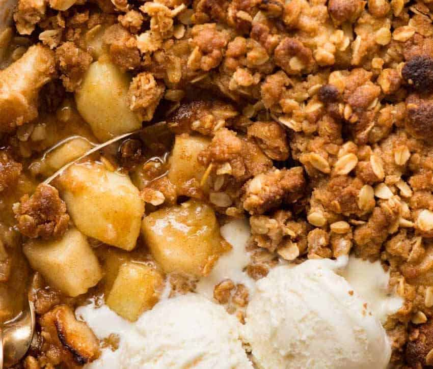 Overhead photo of Apple Crumble showing the warm, cinnamon apple filling, topped with scoops of vanilla ice cream
