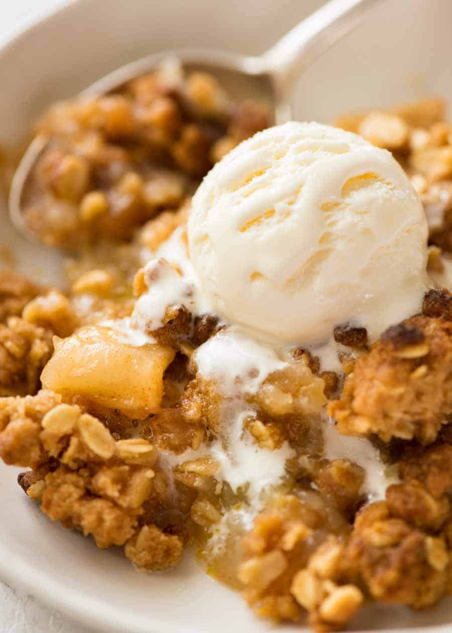 Close up of Apple Crumble in a rustic white bowl with a scoop of vanilla ice cream, ready to be eaten