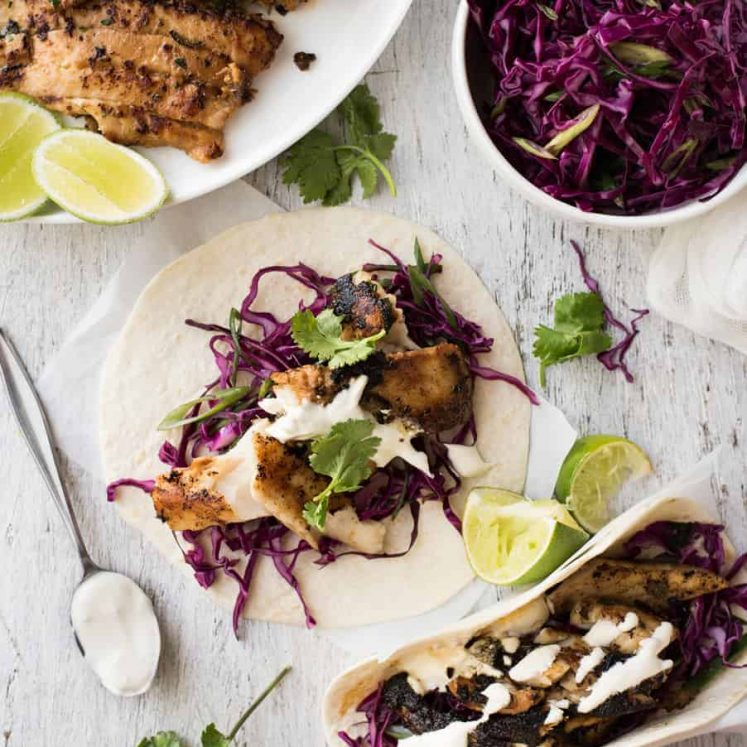 Fish tacos on a table with red cabbage slaw