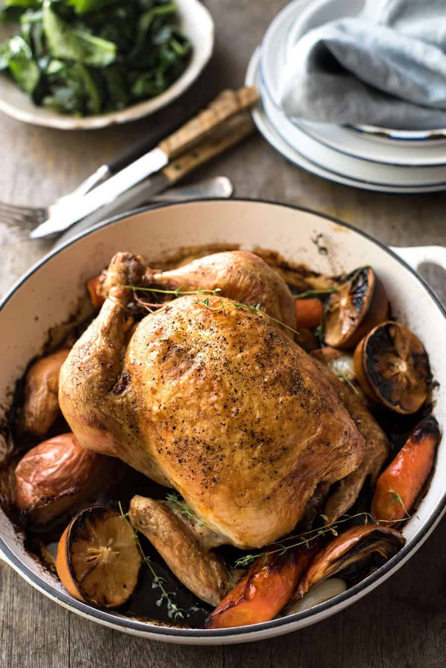 Classic Roast Chicken sitting on top of roast vegetables in a round white shallow casserole pan.