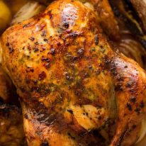 Overhead photo of golden Roast Chicken with crispy skin, fresh out of the oven, bathed in garlic-herb-lemon butter.