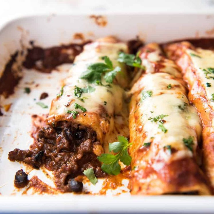 Close up of Beef Enchiladas with an extra tasty, saucy filling, smothered with a homemade Enchilada Sauce in a baking dish.