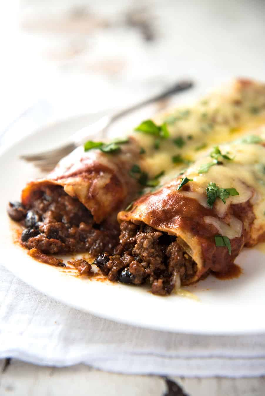 Close up of Beef Enchiladas with an extra tasty, saucy filling, smothered with a homemade Enchilada Sauce.