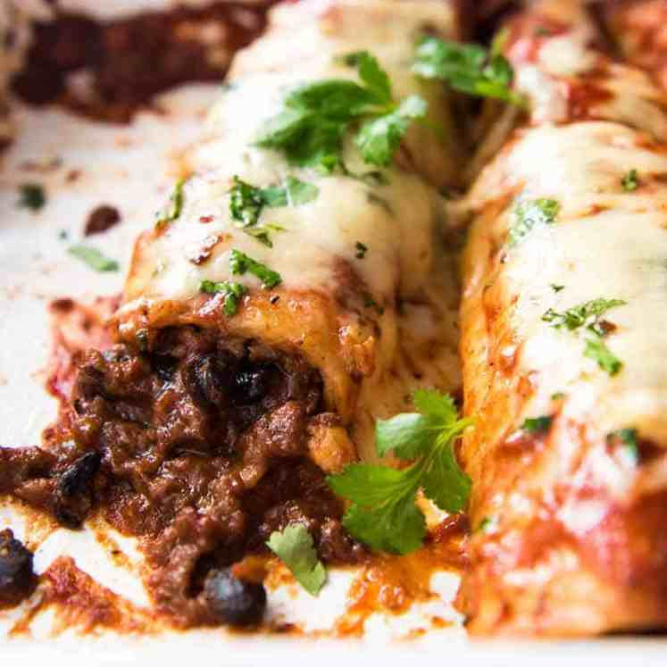 Close up of beef enchiladas in a baking dish, fresh out of the oven