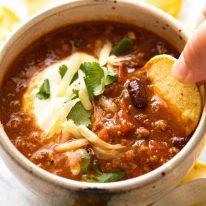 Corn chip being dipped into a bowl of Chili topped with sour cream, grated cheese and cilantro