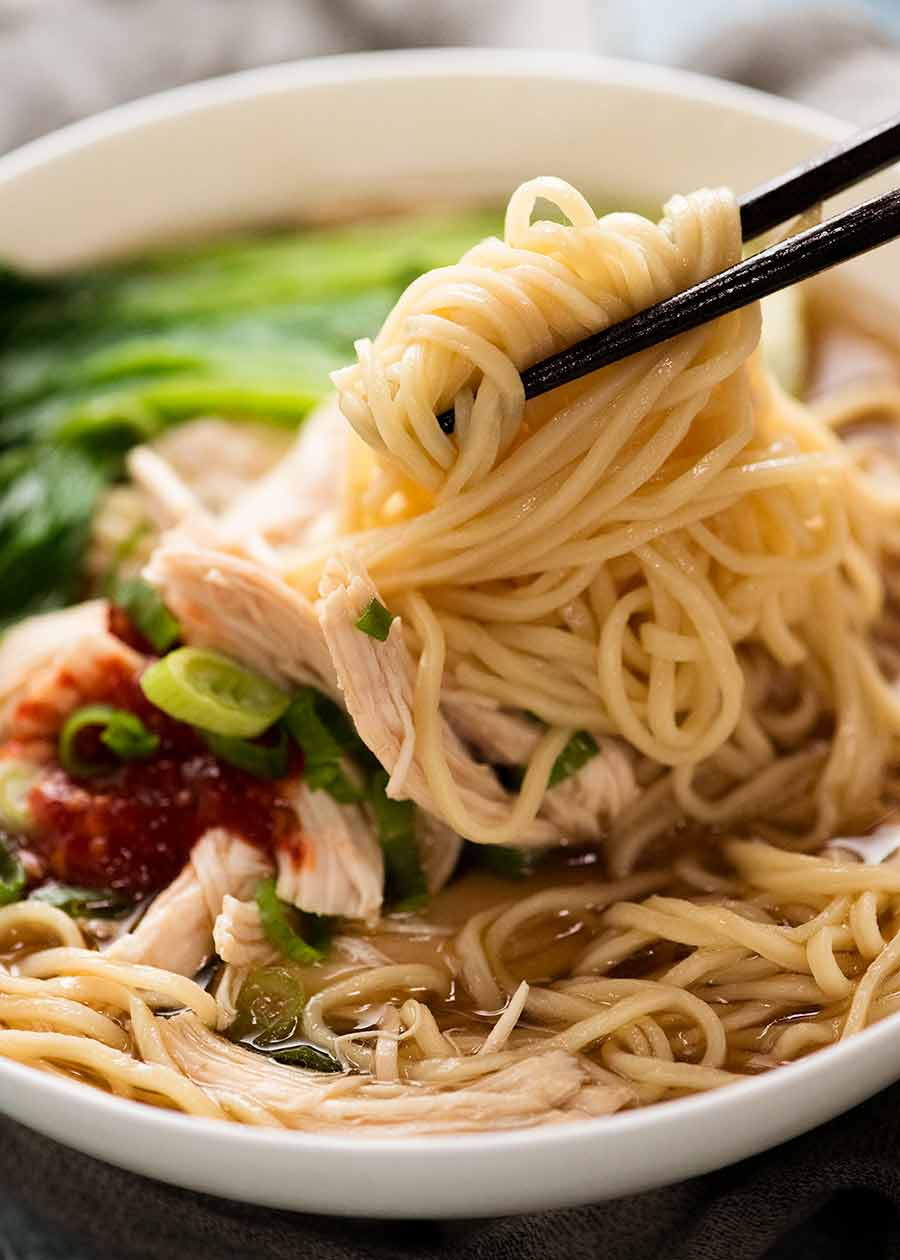 Chopsticks picking up noodles in an Asian noodle soup