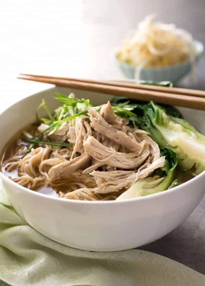 Chinese noodle soup with chicken, bok choi and noodles in a white bowl with chopsticks on the side, ready to be eaten.