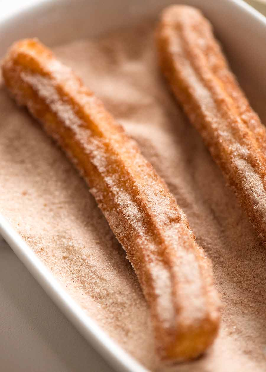 Close up of chutoss being coated with cinnamon and sugar