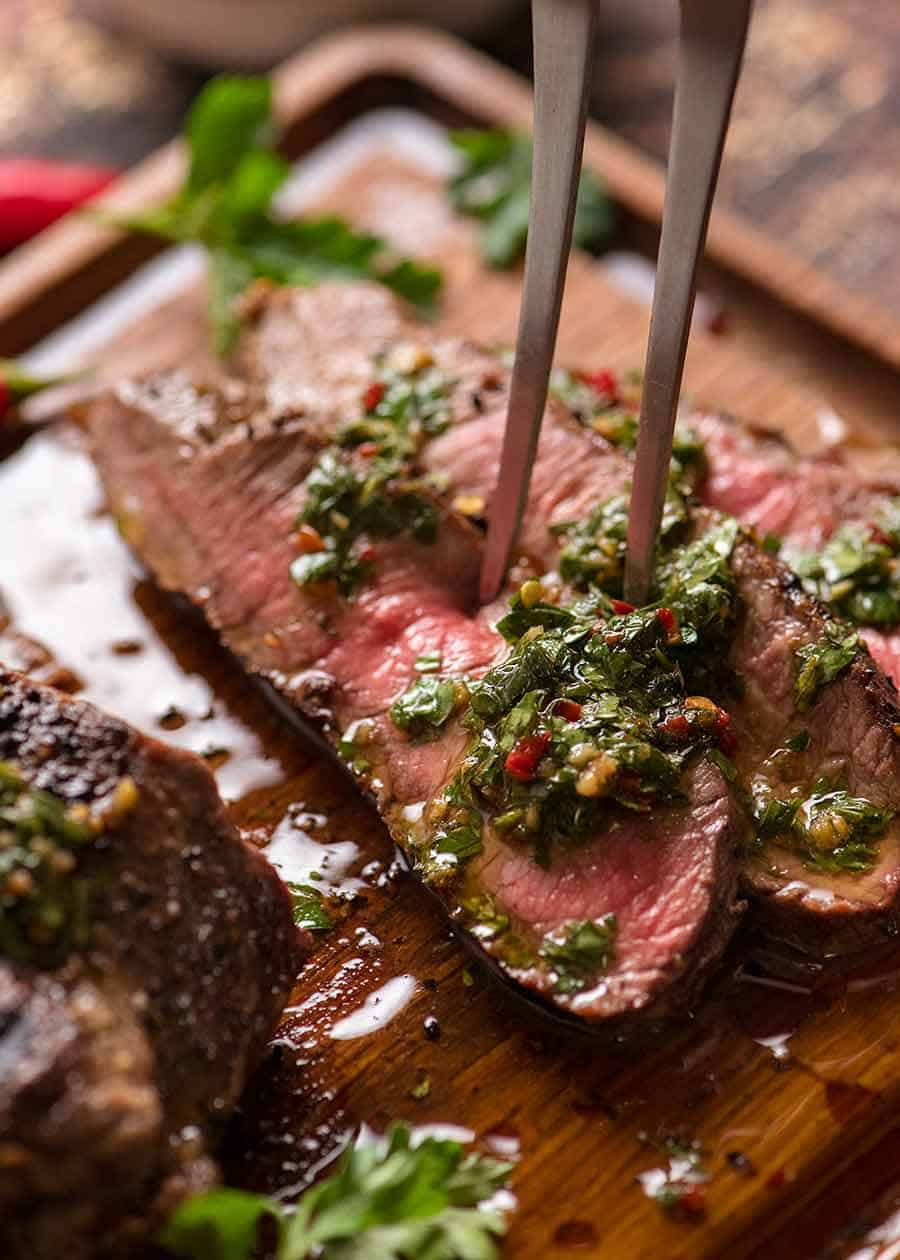 Slices of medium rare cooked steak on a wooden cutting board with Chimichurri Sauce