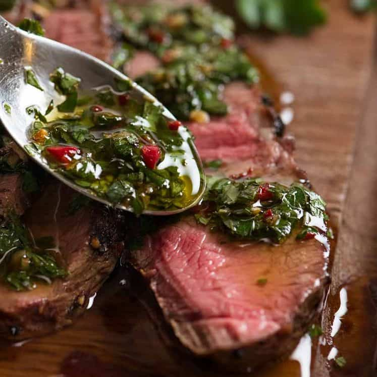 Close up of spoon drizzling Chimuchurri Sauce on steak