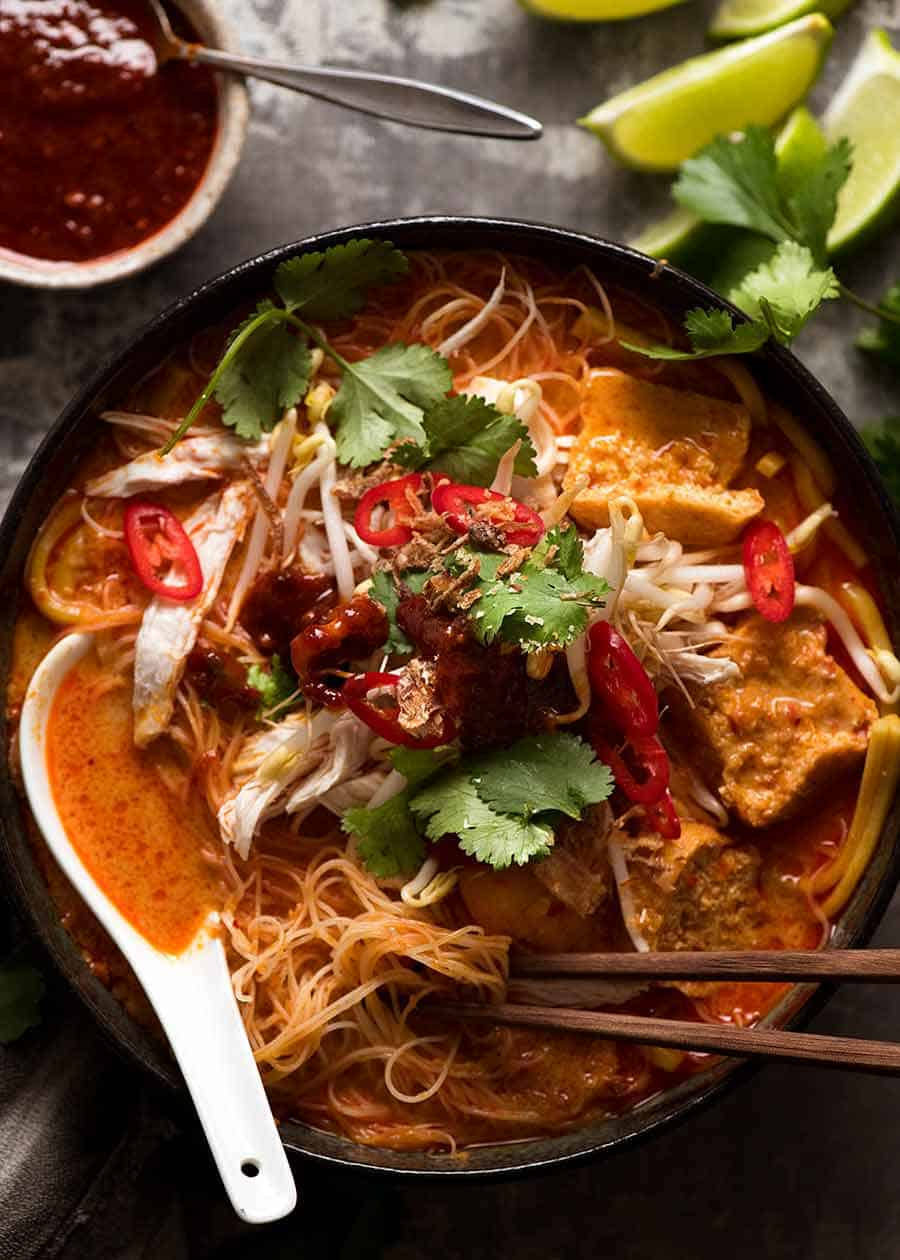 Overhead photo of Laksa in a rustic bowl, ready to be eaten.