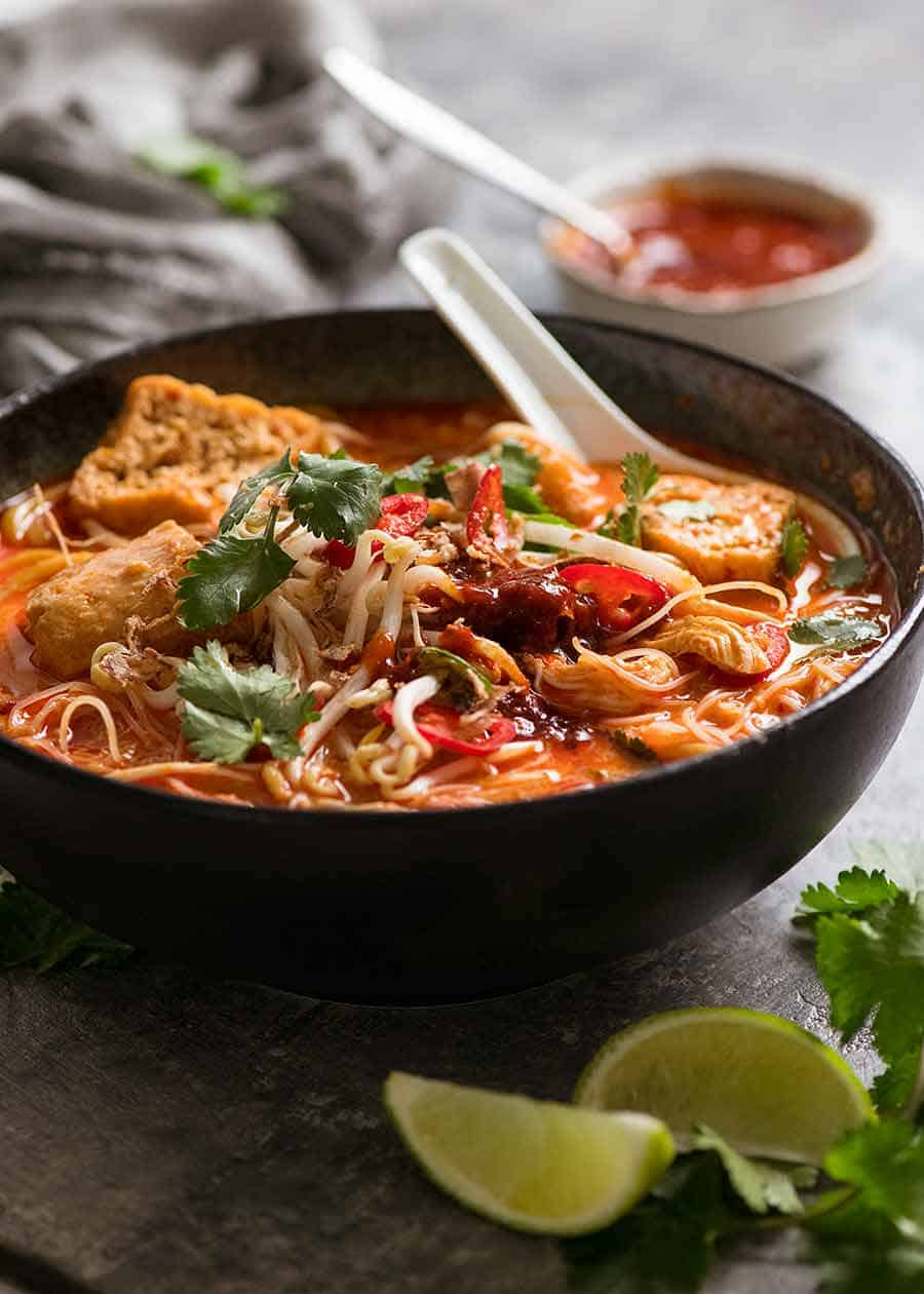 Laksa soup in a black bowl with toppings and Laksa chilli sauce, ready to be eaten
