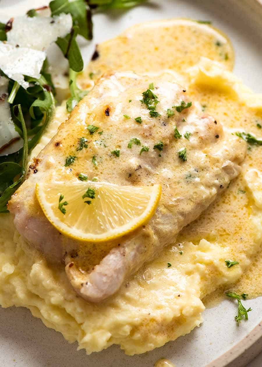Overhead photo of Baked Fish with Lemon Cream Sauce on a plate with mashed potato and a side salad (rocket parmesan balsamic dressing)