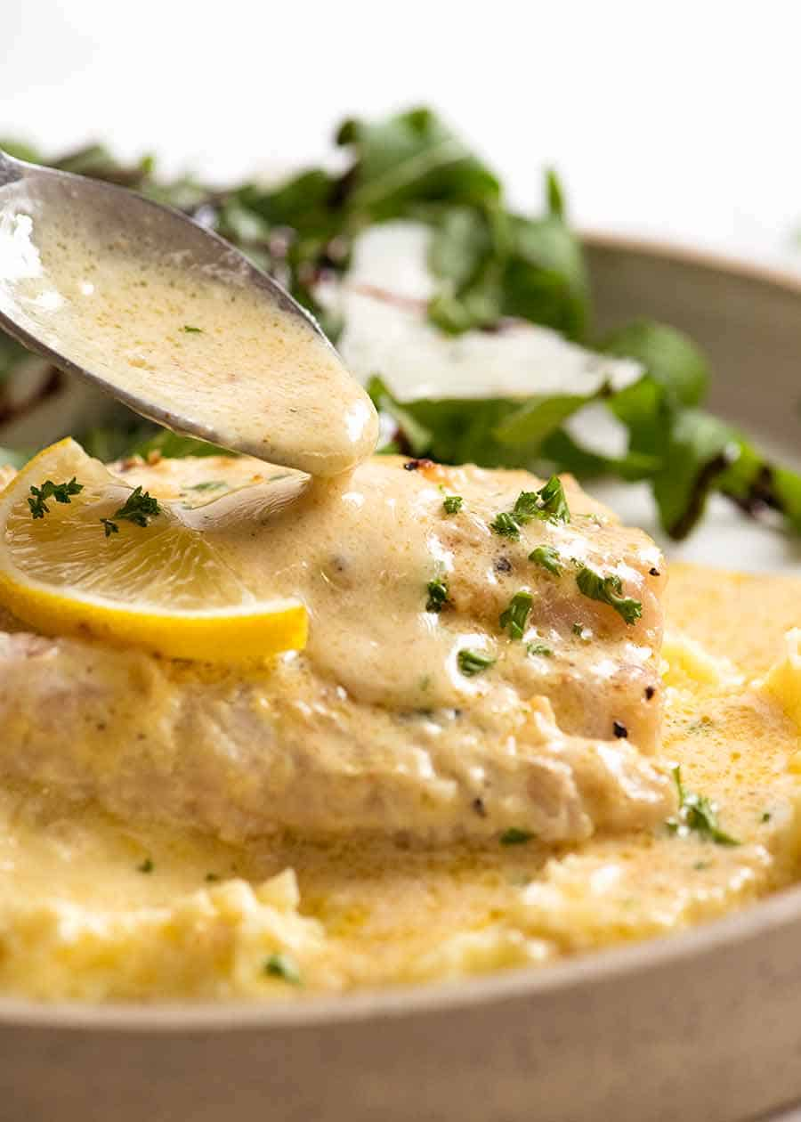 Spoon drizzling Lemon Cream Sauce over Baked Fish (one pan fish and sauce recipe!)