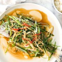 A Chinese Steamed Fish topped with Ginger and Shallots and seasonings, with hot oil poured over it to create a dramatic sizzle and an amazing sauce. So simple, yet so utterly delicious. Steam OR bake the fish! www.recipetineats.com