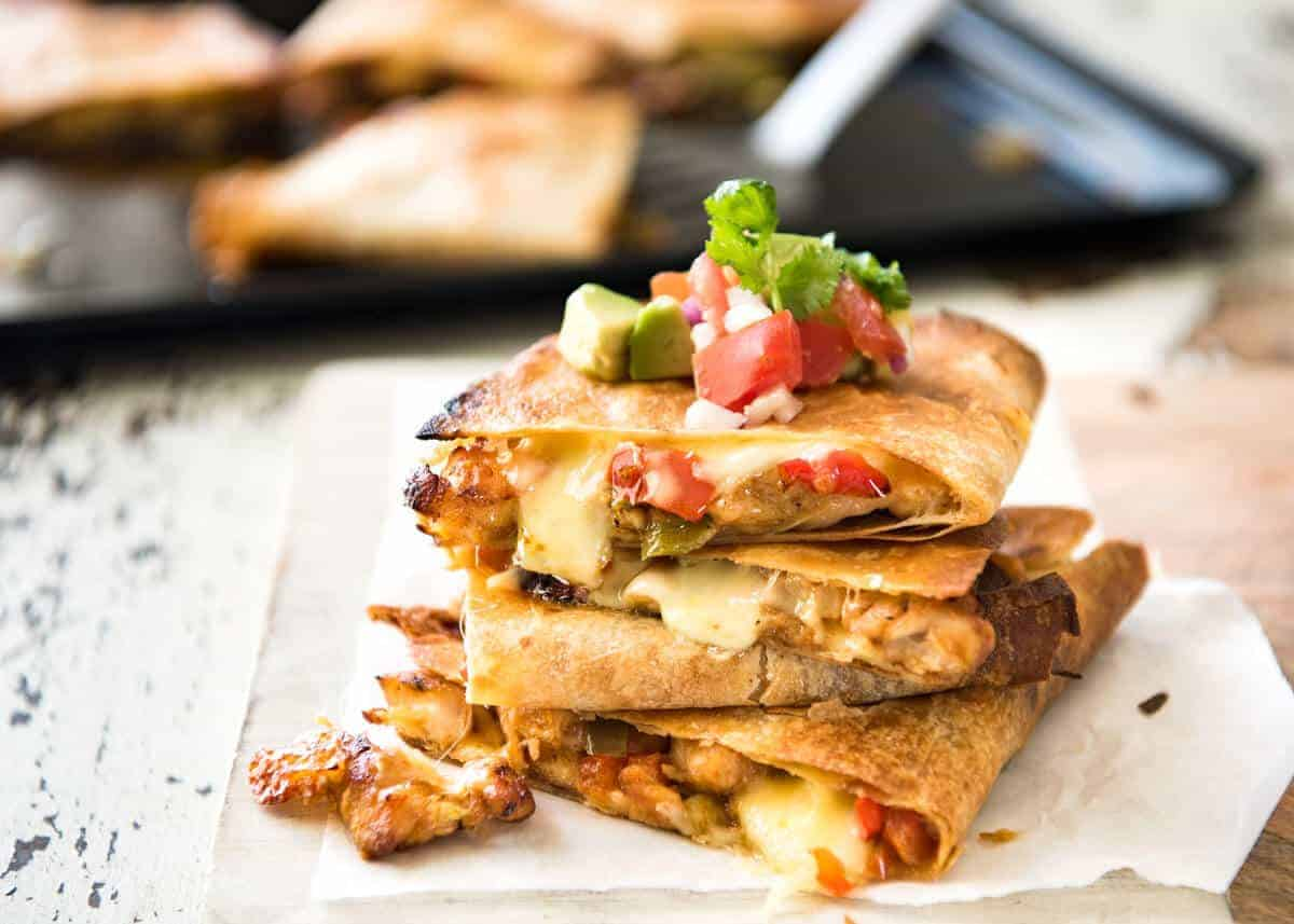 Crispy Oven Baked Chicken Quesadillas - This is how to make multiple Quesadillas at the same time! Crispy on the outside, stuffed with Mexican seasoned chicken and capsicum / bell peppers (and cheese of course!) www.recipetineats.com