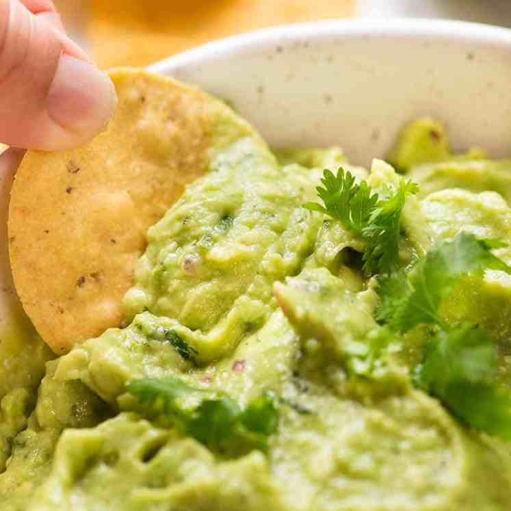 Close up of corn chip being dipped into Guacamole