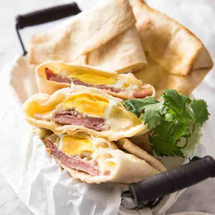 Hot Ham, Egg and Cheese Pockets made with tortillas in a basket, with some cut showing the inside with molten cheese and perfectly cooked egg.