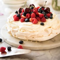 Pavlova decorated with cream and berries