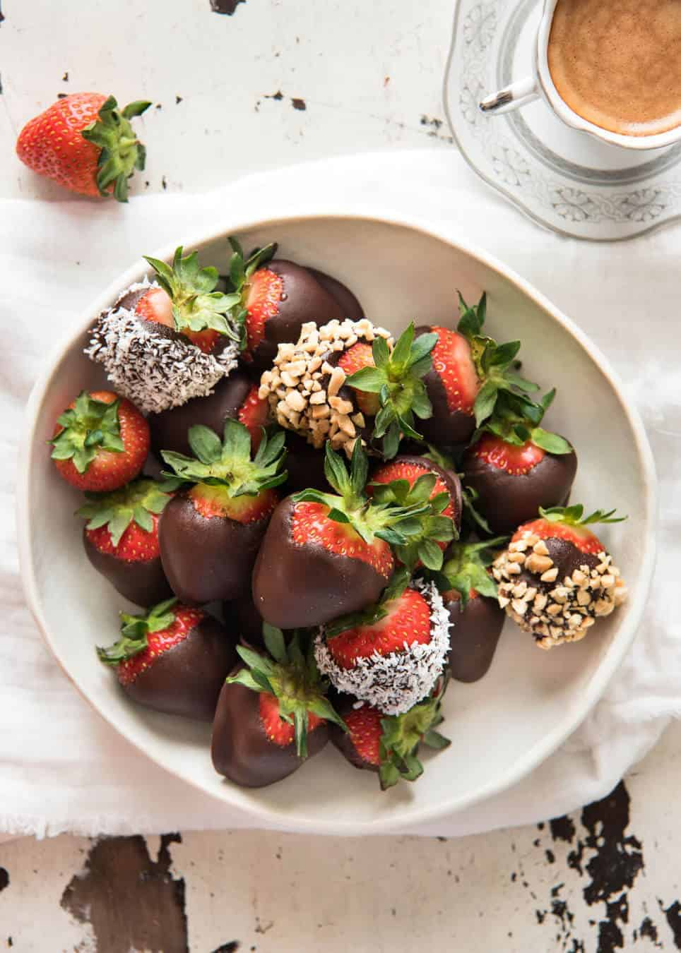 A bowl of chocolate covered strawberries, some coated in nuts and coconut.