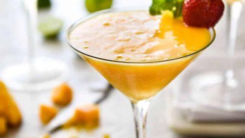 Frozen Mango Daquiris in cocktail glasses, garnished with strawberries.