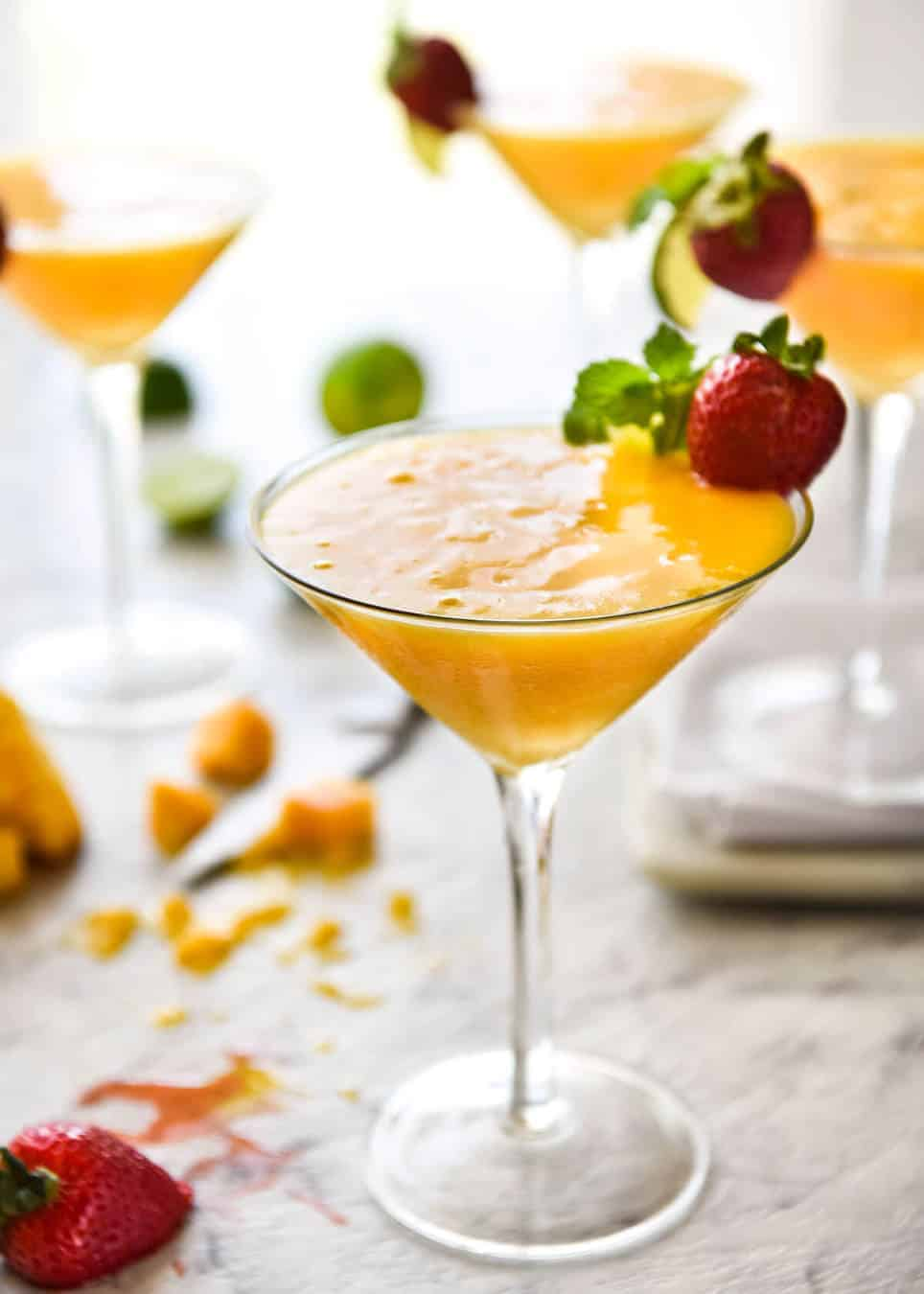 Mango Daiquiris in cocktail glasses garnished with strawberries.