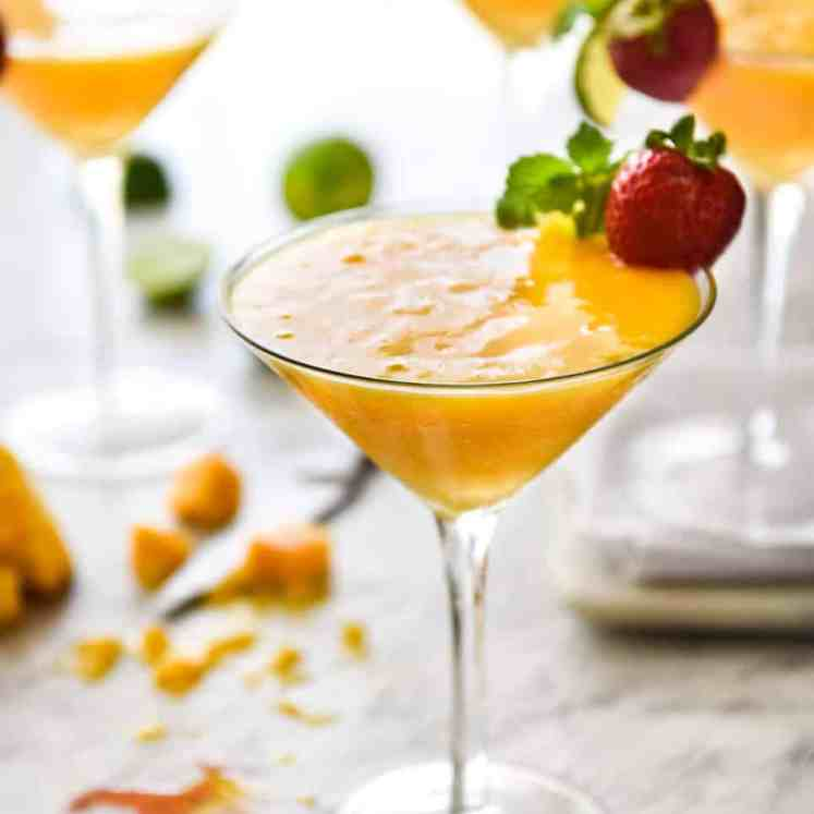 Frozen Mango Daquiris in cocktail glasses, garnished with strawberries.