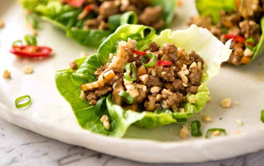 Close up of Chinese Lettuce Wrap being held by a hand, about to be eaten