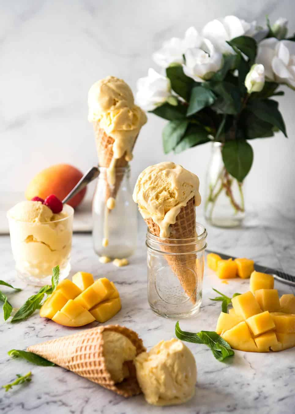 Homemade mango ice-cream in ice cream cones and in cups, with cheeks of cut mango on the side.