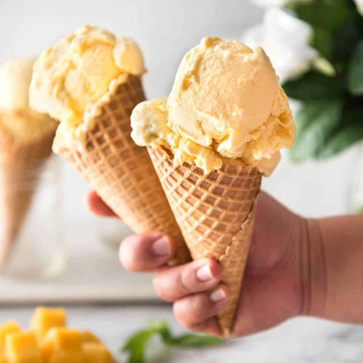 Two ice cream cones with mango ice cream held in a hand.