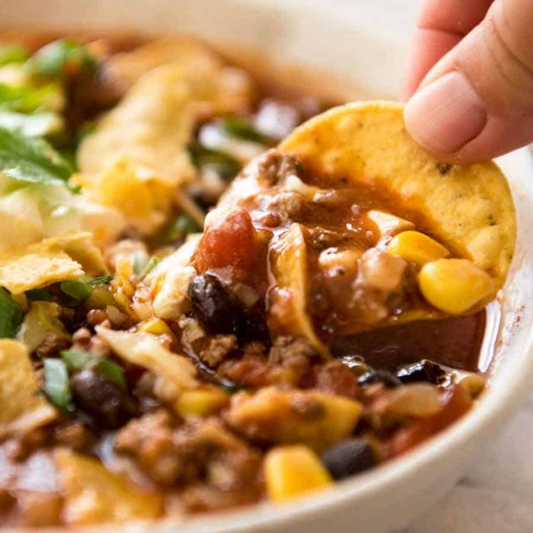 Close up of corn chip being dunked into Taco Soup