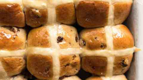 9 Homemade Hot Cross Buns photographed from overhead in a silver tray.