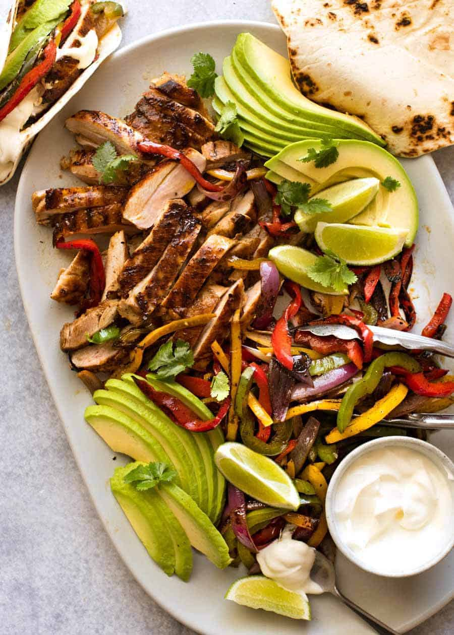 Platter of sliced Chicken Fajitas alongside charred peppers, avocado and warm tortillas, ready to be served.