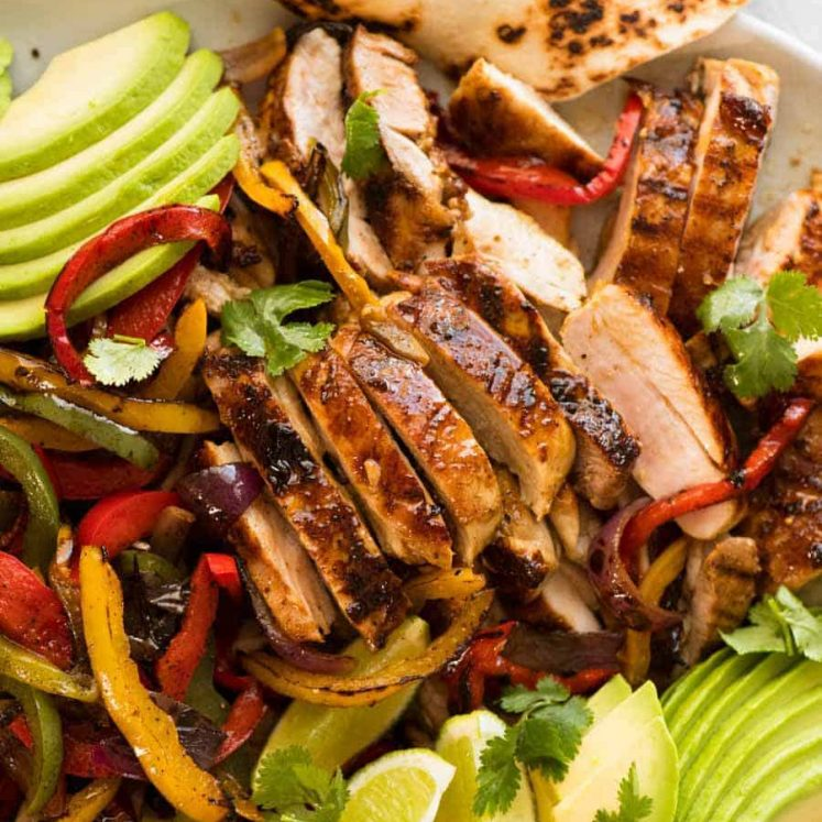 Close up of sliced Chicken Fajitas alongside charred peppers, avocado and warm tortillas, ready to be served.