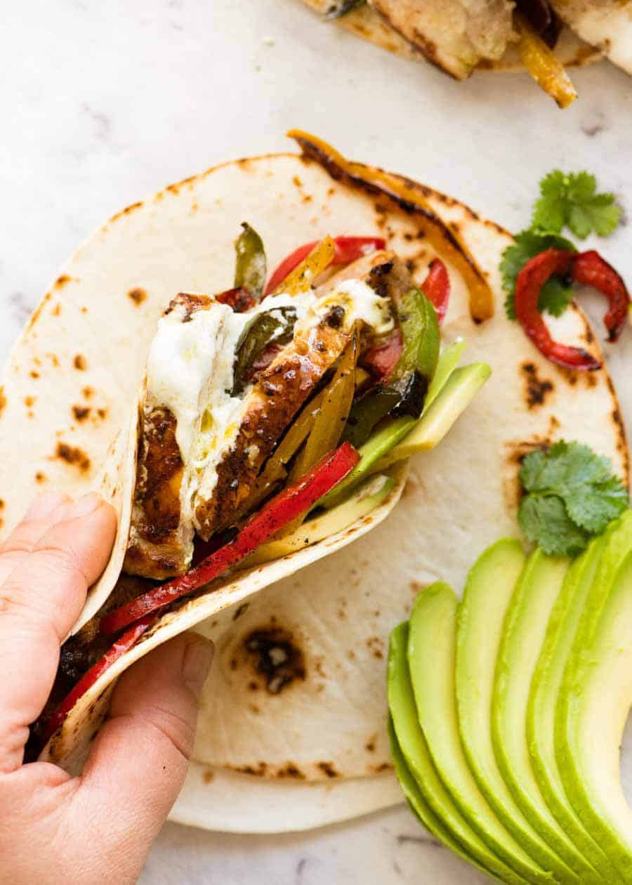 Chicken Fajitas stuffed in a warm tortilla being held but a hand, ready to be eaten.