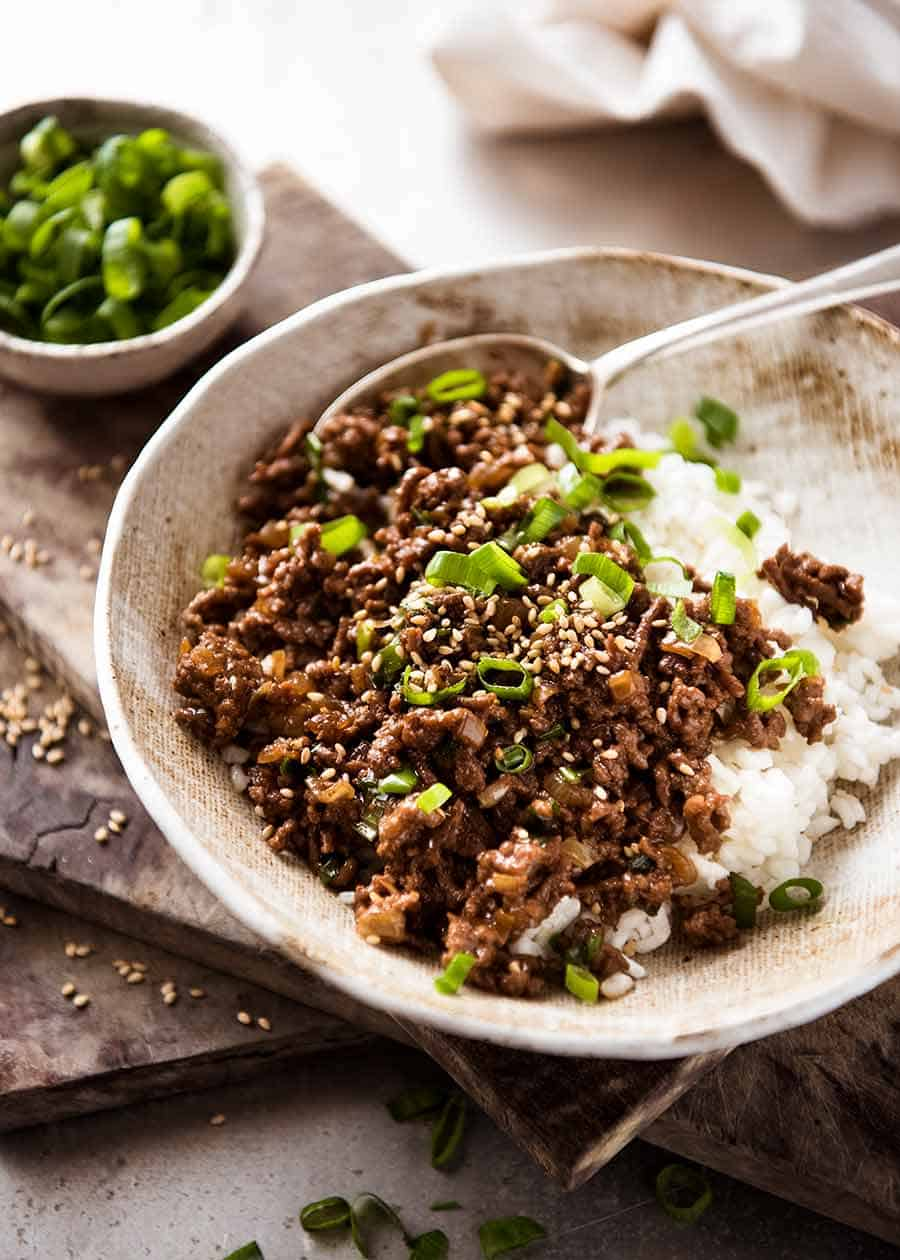 Asian Beef Bowls (ground beef recipe) served over rice garnished with scallions, ready to be eaten
