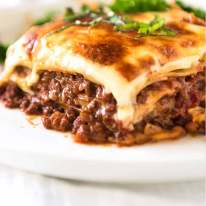 Piece of hot Lasagna on a plate, ready to be eaten